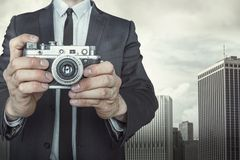Businessman taking a photo with vintage camera. On cityscape background Stock Image