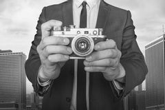 Businessman taking a photo with vintage camera. On cityscape background black and white photo Royalty Free Stock Images