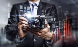 Businessman taking photo with vintage camera . Mixed media Royalty Free Stock Photos