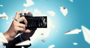 Businessman taking photo with vintage camera . Mixed media Stock Image
