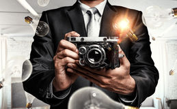 Businessman taking photo with vintage camera . Mixed media Stock Image