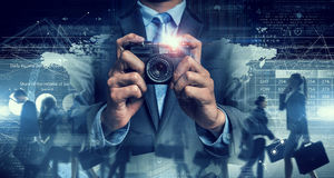 Businessman taking photo with vintage camera . Mixed media Stock Photography