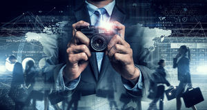 Businessman taking photo with vintage camera . Mixed media Stock Photo