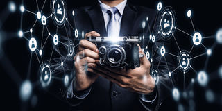 Businessman taking photo with vintage camera . Mixed media Stock Photos