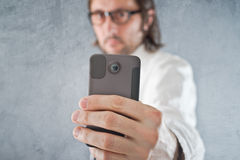 Businessman taking picture with mobile phone Stock Image