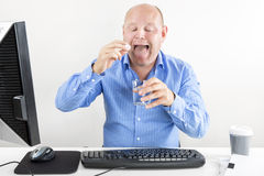Businessman taking pills for headache Stock Images