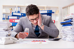 The businessman taking pills to cope with stress. Businessman taking pills to cope with stress Royalty Free Stock Image