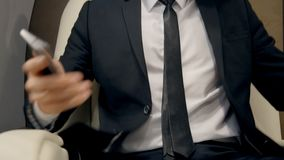 Businessman taking a seat in luxury jet. Man in expensive black suit with tie sitting to the comfortable white leather chair, holding his mobile phone in right stock video
