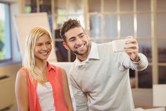 Businessman taking selfie with female colleague Royalty Free Stock Photography