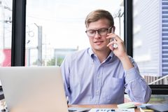 Businessman talk on mobile phone at office. young man call on sm Stock Photo