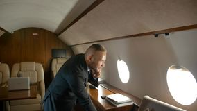 Businessman talk by phone indoor of private jet cabin