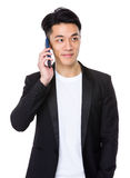 Businessman talk to cellphone and look away Royalty Free Stock Image