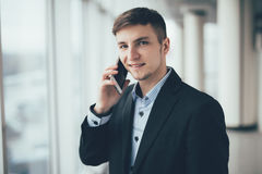 Businessman talk to cellphone and look on camera in office Royalty Free Stock Images