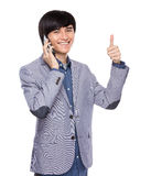 Businessman talk to mobile phone and thumb up Stock Images