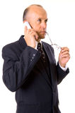 Businessman talking. Businessman holding glasses and talking on the cellphone. isolated on white Stock Photography