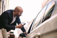 Businessman talking with cab driver on road. Smiling businessman with phone talking on taxi driver in car. Passenger talking with cab driver on road royalty free stock photo