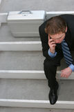 Businessman talking on cell. Overhead view of a businessman sitting on the stairs talking on his cell phone while wearing his business suit Stock Photo