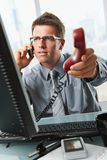 Businessman talking on cell holding landline. Businessman with glasses busy talking on mobile phone handing over landline call to answer in office Stock Photo