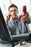 Businessman talking on cell holding landline. Businessman with glasses busy talking on mobile phone handing over landline call to answer in office Royalty Free Stock Photo