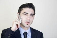 Businessman talking on cell phone. Good-looking businessman talking on cell phone stock photo