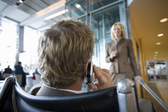 Businessman talking on cell phone in airport terminal Royalty Free Stock Images