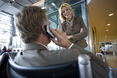 Businessman talking on cell phone in airport terminal Stock Image