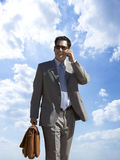 Businessman talking on cell phone with background of clouds in blue sky Stock Photo