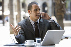 Businessman talking on cell phone in cafe Stock Images