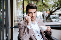 Businessman talking on cell phone and drinking coffee in cafe Royalty Free Stock Images