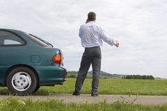 Businessman talking on cell phone beside his car Stock Images
