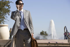 Businessman talking on cell phone outdoors Stock Image