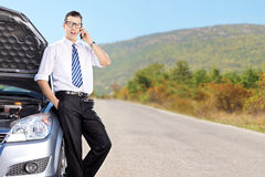 Businessman talking on cell phone and sitting on a car Stock Image