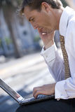Businessman talking on cell phone and typing on laptop outdoors Royalty Free Stock Images