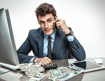 Businessman talking by cell phone while working with PC computer Royalty Free Stock Images
