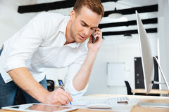 Businessman talking on cell phone and writing in office. Handsome young businessman talking on cell phone and writing in office Royalty Free Stock Image