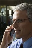 Businessman talking on cellphone. Close up profile of prime adult Caucasian man in suit talking on cellphone Stock Image