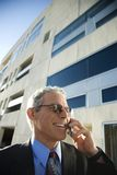 Businessman talking on cellphone. Prime adult Caucasian man in suit smiling and talking on cellphone in urban setting Stock Image