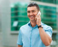 Businessman talking on the cellphone. Handsome businessman talking on the cellphone. He is dressed in a blue plaid shirt. Sunglasses on his head Royalty Free Stock Photo