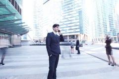 Businessman talking on cellphone. Handsome businessman talking on the cellphone outside office building Stock Images
