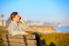Businessman talking on cellphone outdoors,  park bench by ocean Stock Photography