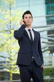 Businessman talking on cellphone outdoors. Portrait of a businessman talking on cellphone outdoors Stock Images