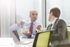Businessman talking with colleague while eating lunch in boardroom during meeting at office stock photography