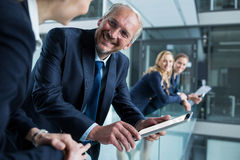 Businessman talking with colleague while holding digital tablet Stock Image