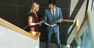 Businessman talking with female colleague in office stairway. Two business people walking up the stairway and discussing work. Businessman talking with female stock images