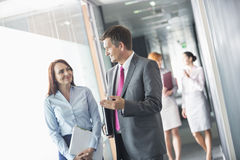 Businessman talking with female colleague while walking in office corridor Royalty Free Stock Photo