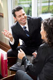 Businessman talking with female Hispanic coworker Stock Photography