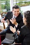 Businessman talking with female Hispanic coworker Stock Photos