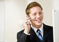 Businessman talking on headset. Businessman talking on a headset Royalty Free Stock Images