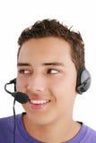 Businessman talking on headset. Smiling businessman talking on headset against a white background Stock Images