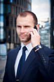 Businessman talking on his cellphone while walking outdoors. In front of a modern office building Stock Photography